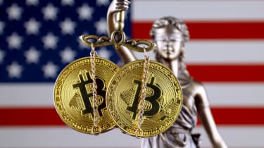 Two bitcoins held by Lady Justice in front of a US flag