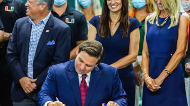Ron DeSantis signing a bill at a desk with standing people behind him