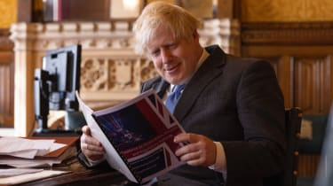 Boris Johnson reading the report prepared by a special taskforce of Conservative MPs