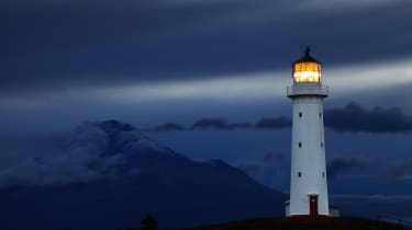 Lighthouse in front of a dark cloudy background