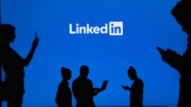 Shadows of people using phones in front of a LinkedIn sign