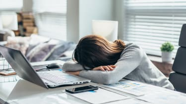Visually stressed out woman with her head laying on a desk in front of her computer