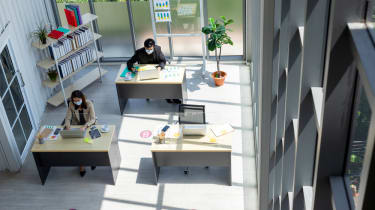 An office with reduced desk space and workers