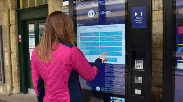 Woman purchasing ticket from Northern Railway's self-service vending machine