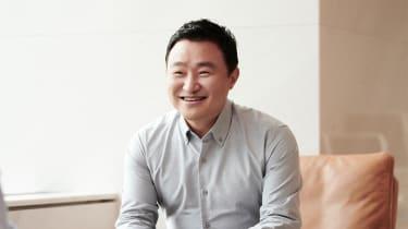 TM Roh in light grey shirt, smiling