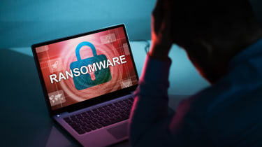 RAnsomware message on a computer screen with person sitting in front of it