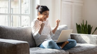 Overjoyed girl sitting on couch at home with open laptop
