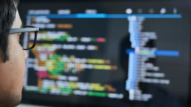 Programmer looking at code on a computer screen