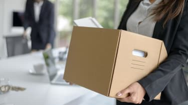 A woman holding a box full of work possessions having left her job