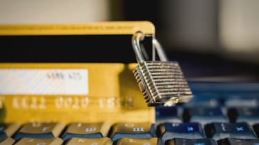 A padlock clipped on a yellow credit card perched on a keyboard