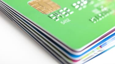 A stack of six credit cards and the top card is green
