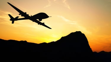 A military drone flying over mountains on sunset background
