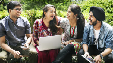 A group of students talking around a laptop