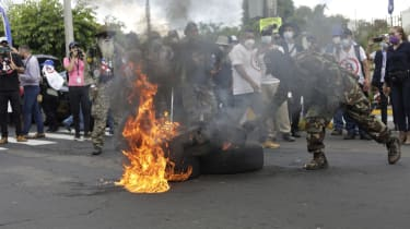 A protester setting fire to an object in San Salvador, El Salvador, in September 2021, with a crowd behind them
