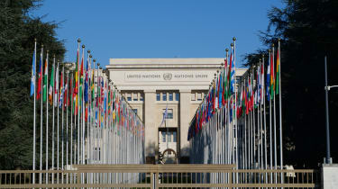 A view of the United Nations building with each nation flag lined up outside beneath a blue sky