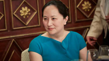 Meng Wanzhou in blue dress sitting at a table at conference in Milan in May 2018