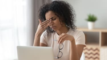 A woman looking stressed while sitting in front of laptop