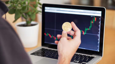 Someone checking online crypto markets while holding a coin