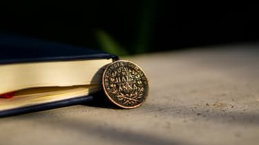 An ancient East India Company coin on a desk next to a leather-bound book
