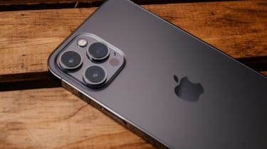 Black iPhone 13 Pro on a dark wood surface