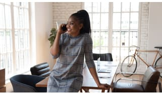 A Black businesswoman happily talking on the phone in front of a boardroom table