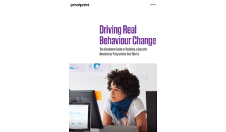 Driving real behaviour change - whitepaper from Proofpoint - woman with scarf sitting at computer