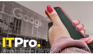 A hand holding a smartphone with Google HQ in the background