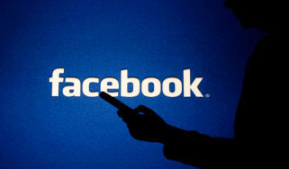 A shadowy figure using a smartphone in front of the Facebook logo
