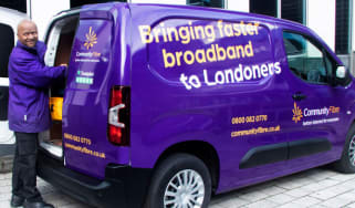 "A Community Fibre employee stands next to the company van with the slogan ""Bringing faster broadband to Londoners"""