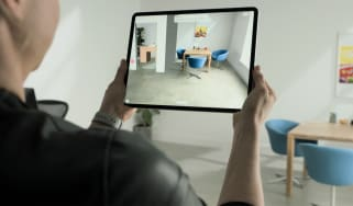 A man holding up an iPad in a dining room space