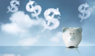 A white piggy bank sits on a reflective surface while clouds in the shape of dollar signs float in the sky behind it