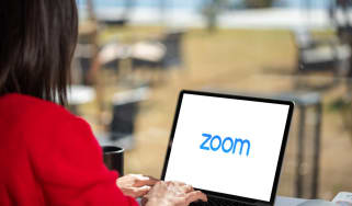 A woman using a laptop with the Zoom logo on the display