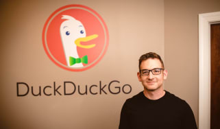 DuckDuckGo CEO Gabriel Weinberg standing in front of his company's logo