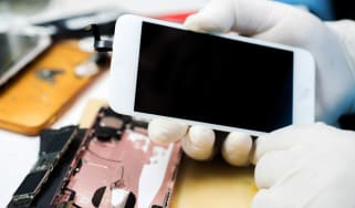 Rubber gloved hands disassembling an iPhone