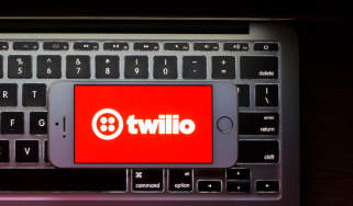 The red Twilio logo on an iPhone screen that's sat on top of a MacBook keyboard