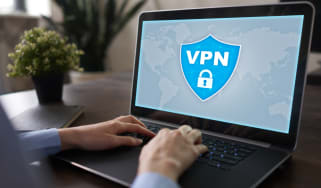 A generic VPN logo shown on a laptop display while a person types