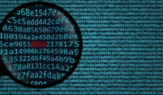 The word DDoS in red shown through a magnifying glass