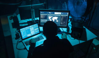 A group of hackers using malware tools in a dark room