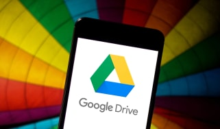 Google Drive displayed on a smartphone in front of a multi-coloured umbrella