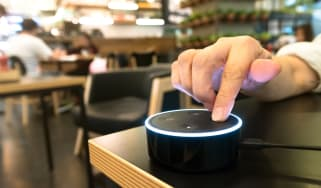 An Amazon Eco Dot being pressed by a user