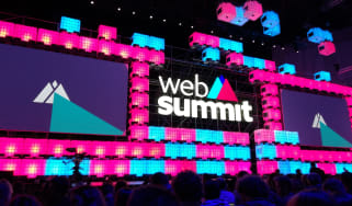 A screen displaying the Web Summit logo in a darkened room