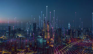 A cityscape at night with data streams riding into the sky