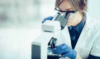 A female scientist looking through a microscope in a laboratory