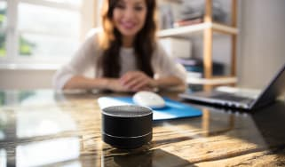 A businesswoman working from home and smiling at a smart speaker