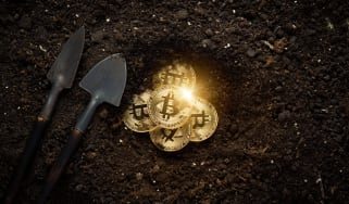 Two shovels next to Bitcoins being uncovered in mud to depict cryptocurrency mining