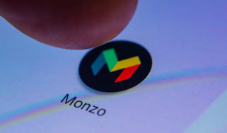 A finger pressing Monzo's App icon on a phone