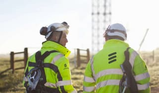 Two employees in helmets and hi-vis jackets sporting the Ericsson logo