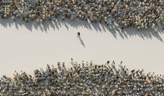 An overhead shot of a woman standing in the gap between two crowds of men