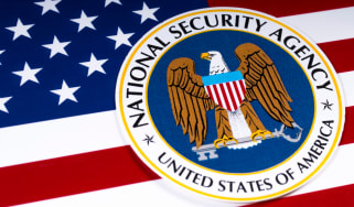The logo of the National Security Agency in front of the US flag