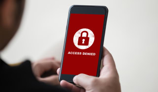 """A man holding a smartphone displaying the message """"access denied"""" in white lettering on a red background"""